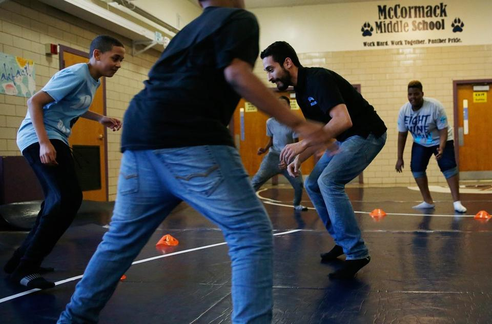 Wrestling coach Jose Valenzuela, center, is a teacher who founded a nonprofit wrestling program for city kids.
